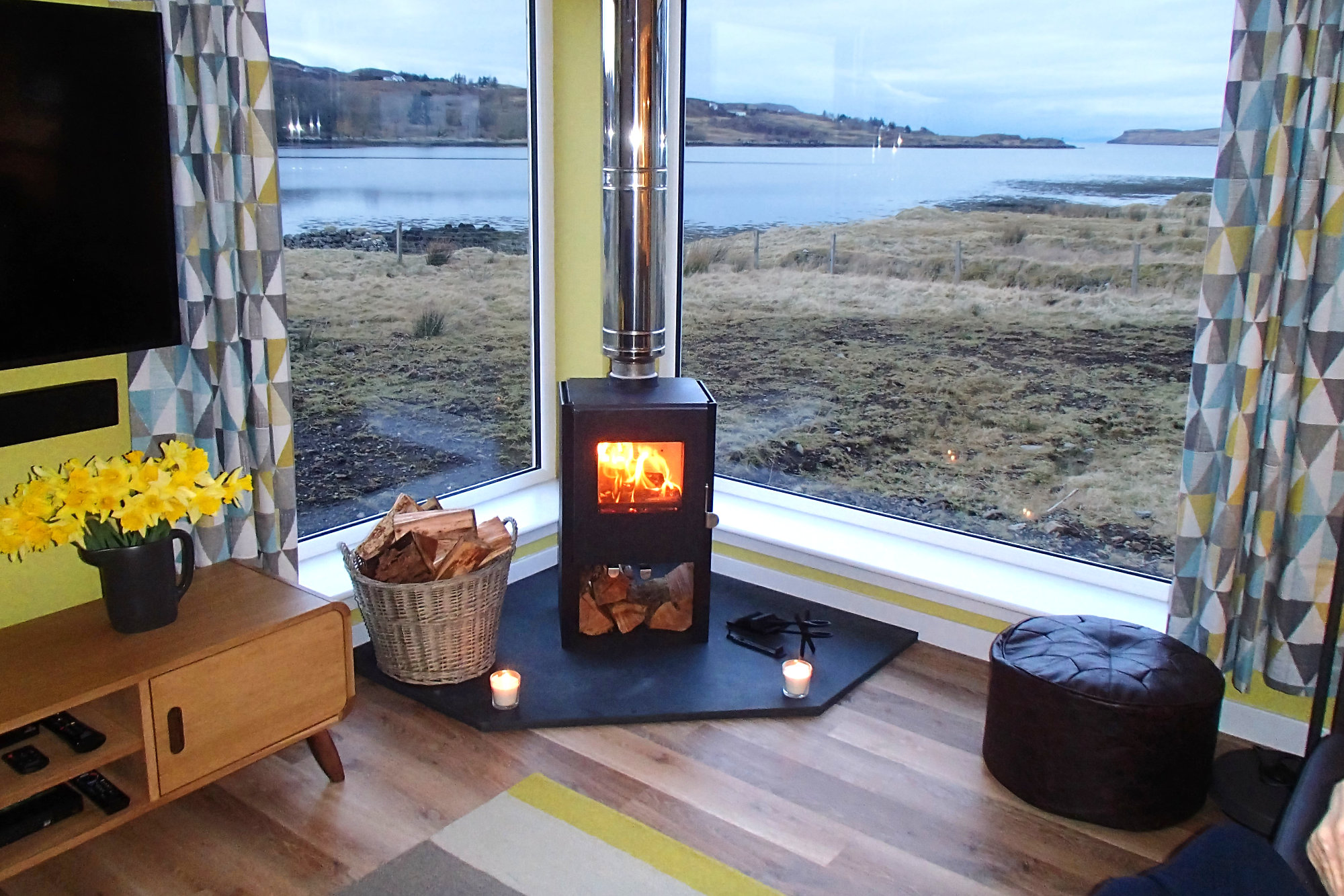 Cosy up by the log burner, but still enjoy the views of the setting sun.