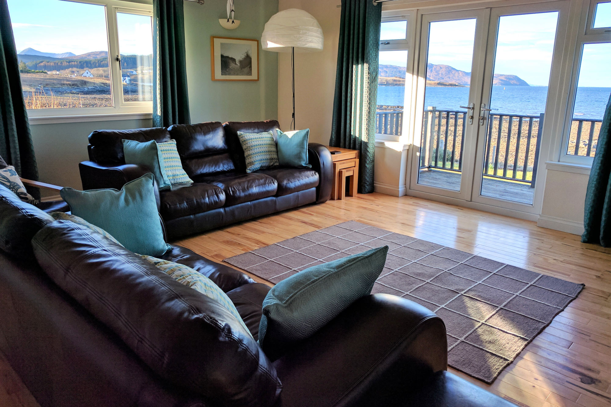 Dual aspect Sitting room with broad views to the bay and double doors to the front decking.